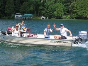 family in a boat at pineridge resort on deer lake in grand rapids, minnesota