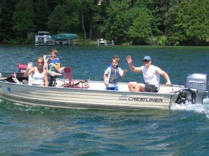 Family on a boat waving at the camera