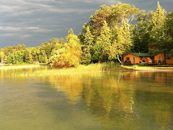 sunset on the lake shore reflecting off the Pineridge Resort Cabin