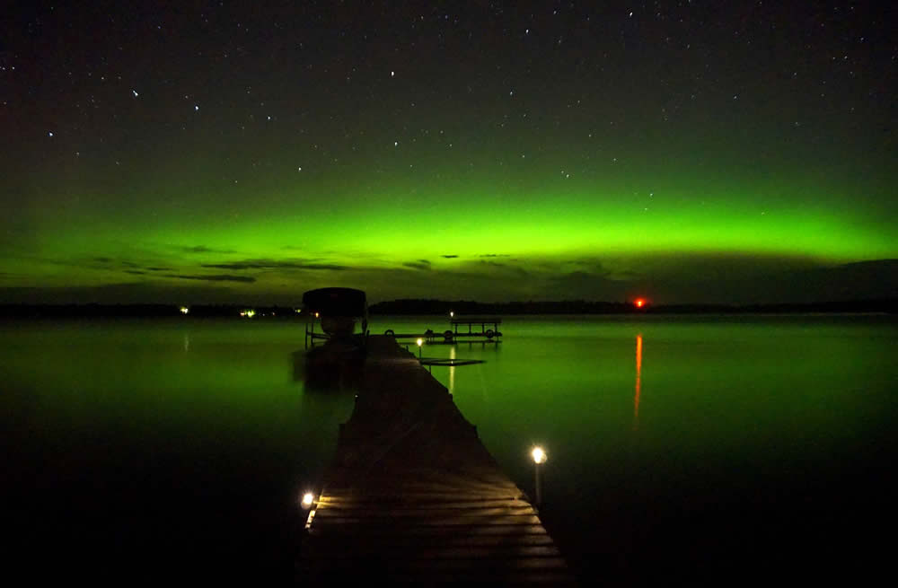 Northern lights over a lake with a dock